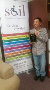 Patrick holding his plaque for AT Advocate of the year